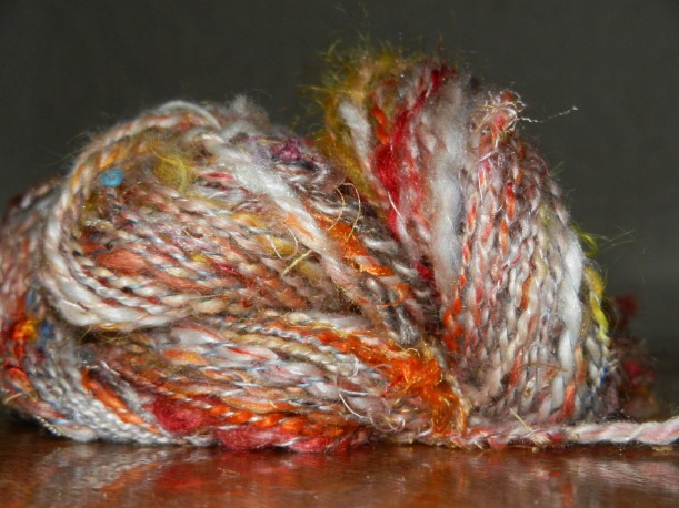 Orange, red, white, yellow skein of yarn with hints of blue. Made of wool, mohair, camel, firestar, and other fibers.