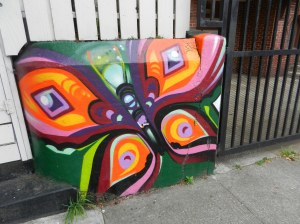 street mural, butterfly, orange and purple, on a retaining wall