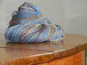 Skein of mostly blue and bronze handspun yarn made of yak, silk, tencel, various wools, silk fabric scraps and threads, leftover yarn.