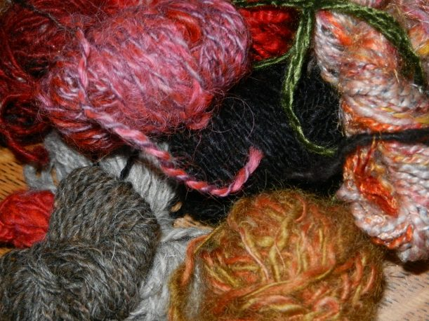 Gratuitous yarn photo. Note the orangy ball at the bottom with the gawd-awful loose twist. An early handspun.