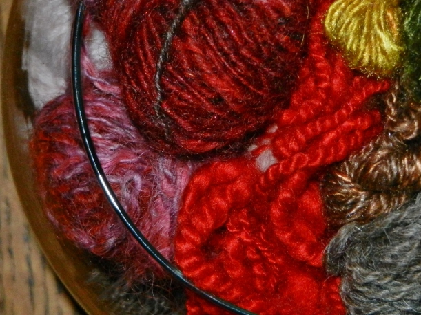 Close up of small red, pink, yellow, green balls of handspun yarns in a bowl.