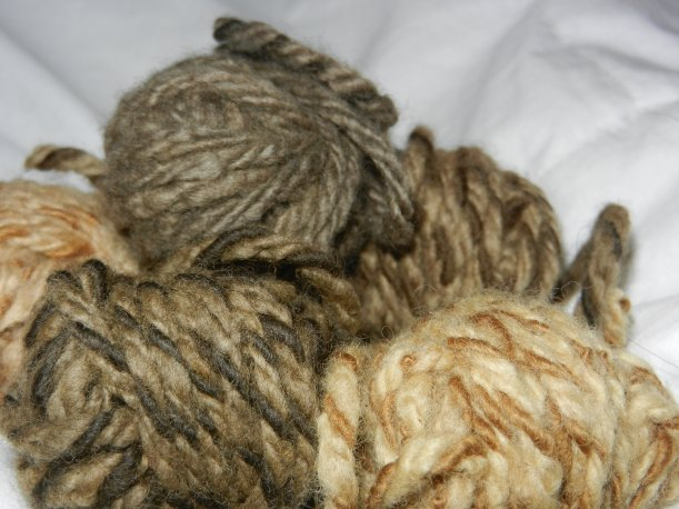 small pile of yarn balls in various rich shades of cinnamon to chocolate