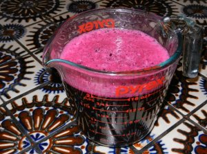 Measuring cup full of dark fuscia bougainvillea dye.