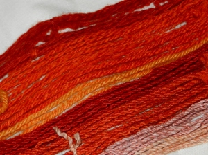 Orange and red silk, cotton, and wool yarn.