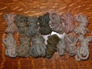 Two rows of seven tiny balls of yarn, from silver to lavender to pink.