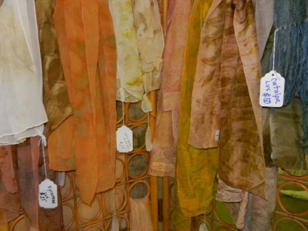 Naturally dyed scarves in rust, yellow, peach, with eco-printed leaves and flowers.