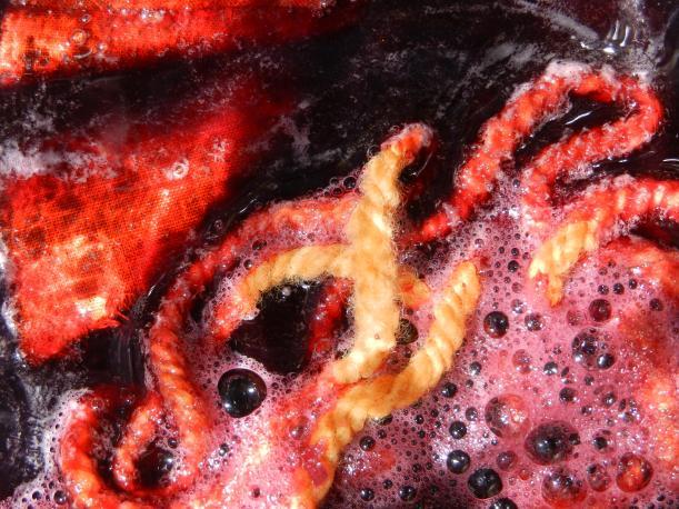 bright orange rust-mordanted fibers sink into red bougainvillea dye.