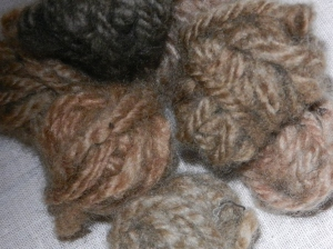 Seven tiny balls of reddish yarn in varying shades.
