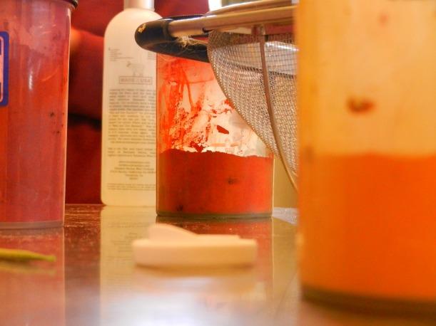 brilliant yellow, orange, and fuscia dye jars with a colandar.