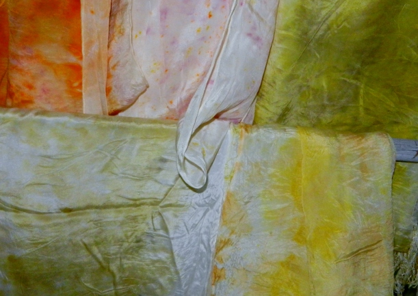 Bright orange, pink, yellow, and green silk scarves, hand-dyed with natural dyes.
