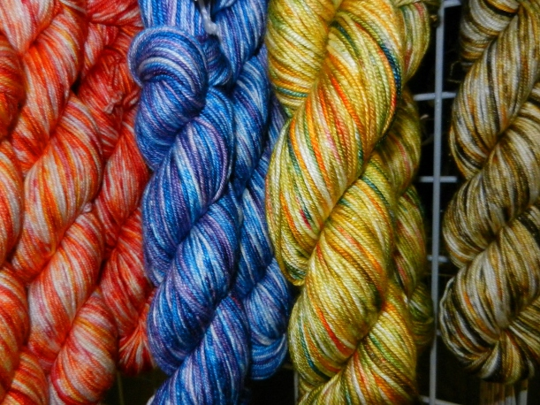 Red, blue, yellow-gold, and green-gold skeins of hand-dyed yarn.
