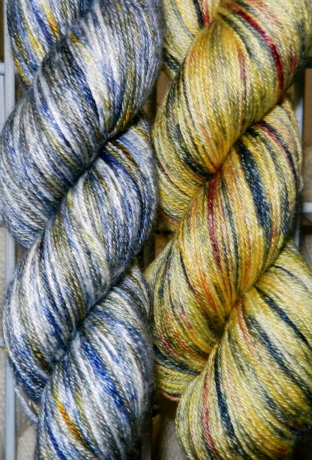 Blue-silver and gold-rust skeins of hand-dyed yarn.