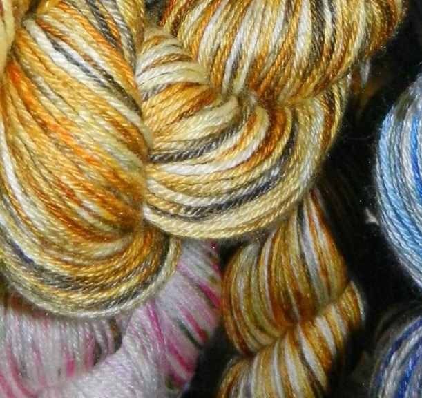 Rust-gold-silver and pink skeins of hand-dyed yarn.