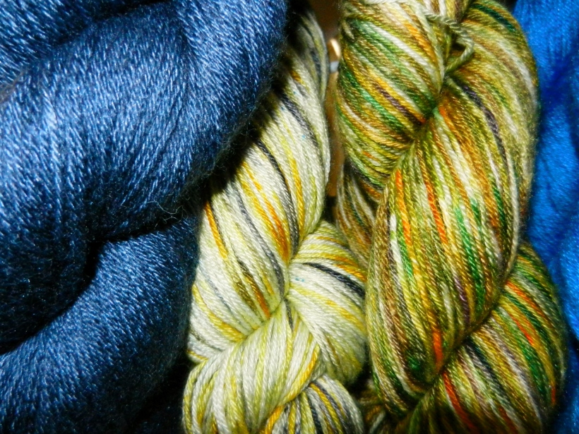 Blue, cream-gold-silver, and green-gold skeins of hand-dyed yarn.