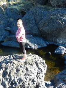 My neice on black lava, overlooking the swimming hole.