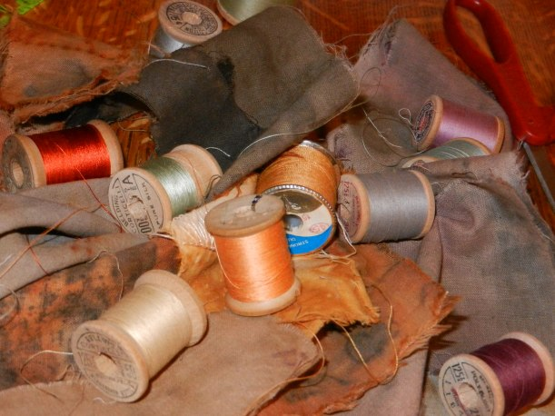 Threads of various bright and subtle colors on top of many-hued naturally dyed fabrics.