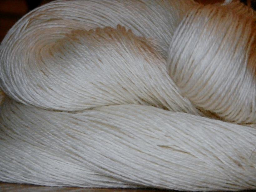 Skein of fine handspun spun ivory Merino wool.
