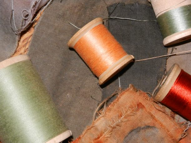 Grey, charcoal, and rust-colored naturally dyed fabric samples with orange and olive thread.