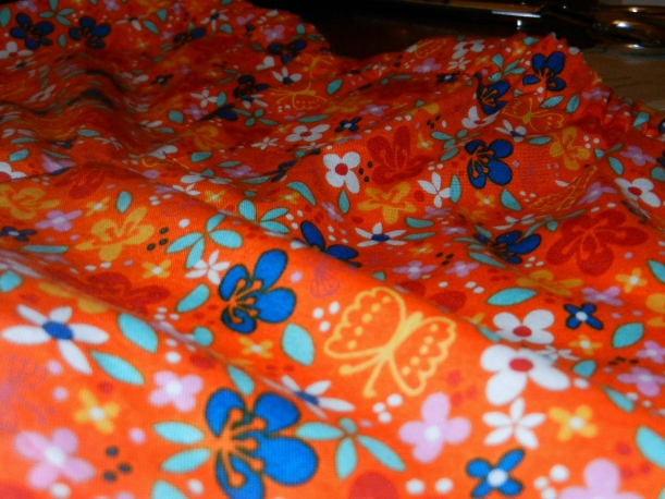 Closeup on orange boxer shorts with yellow, blue, and white flowers, and yellow butterflies.
