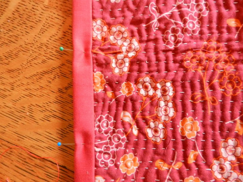 Red-flowered Sashiko cloth and pinned binding