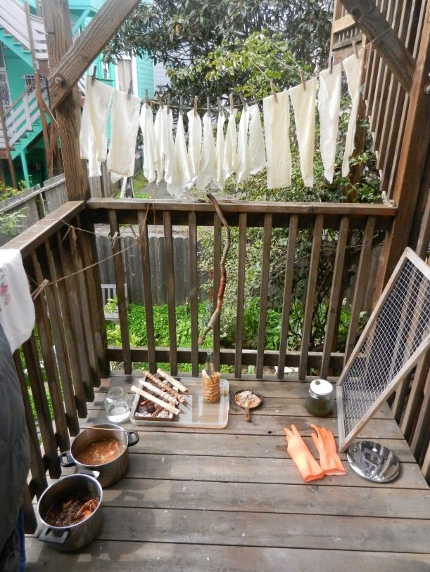 small patio covered in textiles in various stages of dyeing